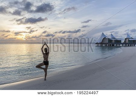 Woman exercise with Yoga on the beach in the morning at W Retreat & Spa Maldives On Fesdhoo Island North Ari Atoll in Maldives