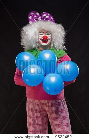 Funny clown with shaggy hair and a cheerful make-up holding a gift
