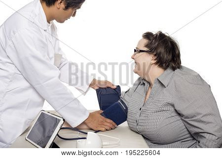 Female patient getting checkup with a doctor using a modern electronic blood pressure monitor. The device is a smart medical gadget and connects to a tablet. The diagnosis is made possible by health insurance.