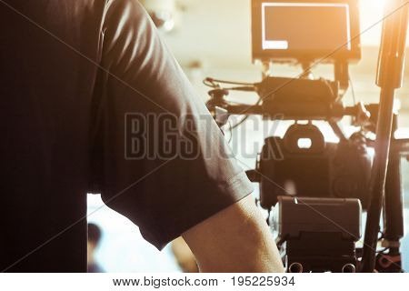 Cameraman with his video camera shooting, Adjusting Camera,film production cre. behind the scenes background.