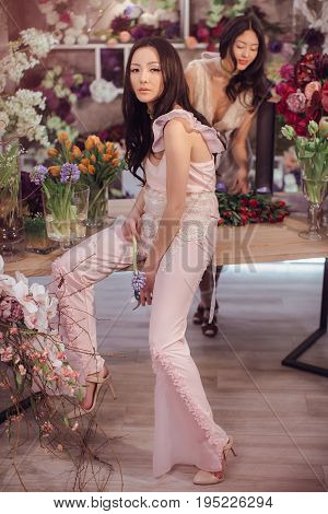 Fashion models in tender dresses posing and looking at camera. Beautiful asian florist girls with flowers in hands against floral bokeh background in flower shop indoors. Two attractive asian females florists working in store.
