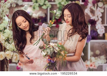 Beautiful asian florist girls making bouquet of flowers for sale against floral bokeh background in flower shop indoors. Two attractive asian females florists working in retail store. 2 playful fashion models in tender dresses posing playing with flowers.