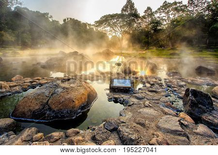 Mineral hot water in hot springs and morning fog background at Chae Son National Park the park is also host to caves and hot springs Lampang Province Thailand