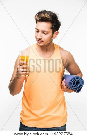 Good looking Indian young man holding yoga or exercise mat and having a sip of fresh juice in a glass post exercise or yoga / asana, isolated over white background