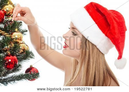 Pretty woman dressed as Santa Claus is standing beside a fir tree, smiles happy and holds a glass ball in her hand. Isolated on white background.