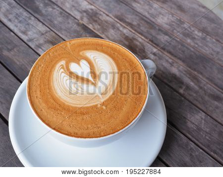 Cup of coffee on the wooden table with latte art, top view with copy space.