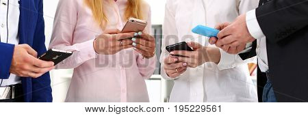 Group Of People Look At Phones In Arms