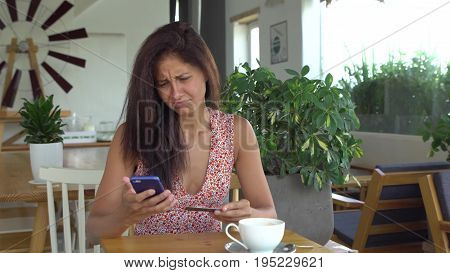 Woman can not make purchase with credit card on mobile phone. Female shopping online in cafe. Girl is sad and dissappointed because of failure. Unsuccessful payment.