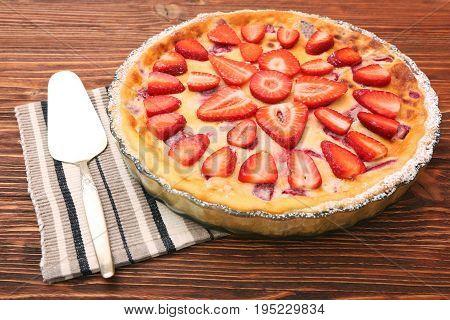 Tart with fresh strawberry on wooden background. Traditional summer dessert.