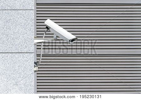 Outdoor Surveillance Camera On Facade Of Building Against Closed Gate