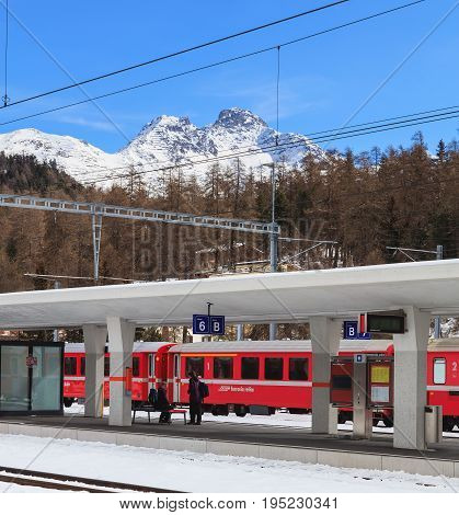 St. Moritz, Switzerland - 3 March, 2017: a platform of the St. Moritz railway station, a passenger train of the Rhaetian Railway at it, mountains in the background. St. Moritz is a municipality in the Swiss canton of Grabunden.