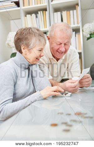 Senior pensioneers with calculator doing finance accounting with joy