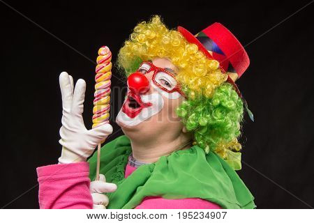 Funny clown in a hat with a big candy