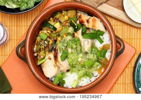Seared Chicken and Tomatillo Salsa in Small Crockery Potl on table.
