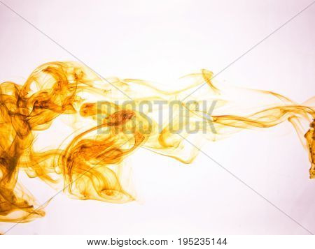 Ink swirl in a water on color background. The paint splash in the water. Soft dissemination a droplets of colored ink in water close-up. Abstract background. Explosion of splashes acrylic ink.