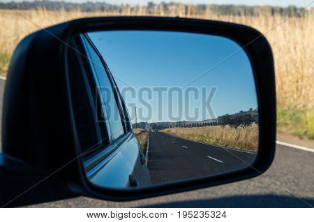 View of a country road in Victoria Australia seen in a car rear view mirror