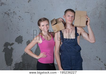 Young family of two loving people parses boxes in the new apartment on the background of a dirty concrete wall