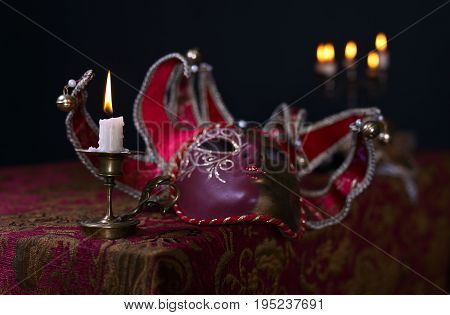 Candle in small brass candlestick and Venetian mask