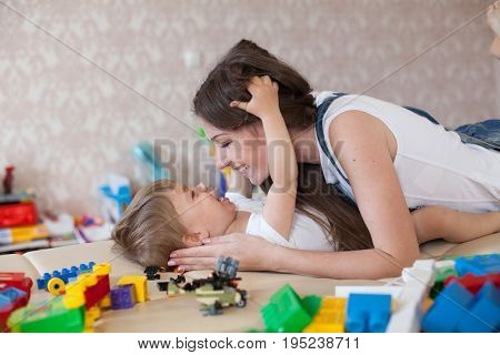mom plays with a little boy with love kisses laughs 2
