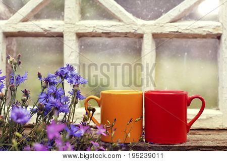 Two mugs with a hot drink and a bouquet of wild flowers on the background of the old window / cozy place for a couple
