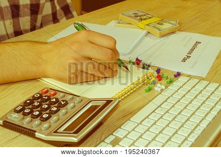 Close up view of bookkeeper or financial inspector hands making report calculating or checking balance. Business plan calculator dollar banknote on the table - Retro color