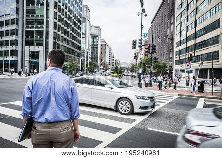 Washington DC, June 2017, United States: Businessman standing at the red traffic light to cross the street. Shoulder man ready to cross the road on the pedestrian strips in Wahington DC's dowtown.