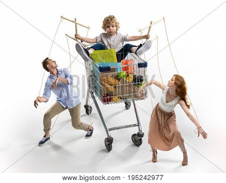 Parents Manipulated By Little Son In Shopping Cart Isolated On White