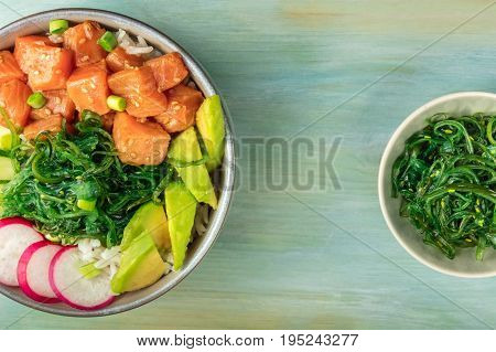 An overhead photo of poke, traditional Hawaiian raw fish salad, with a plate of wakame, sea vegetable, with copy space in between