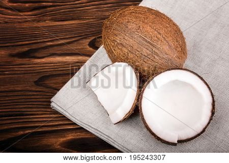Tasteful tropical nuts on a gray piece of cloth on a dark wooden background. Nutritious cracked coconuts on a brown table. Healthful organic summer fruits.