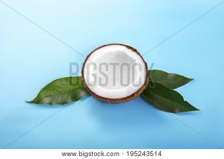 A coco on a bright light blue background. Delicious coconut cut in half. Round white nut on dark green leaves. Ingredients for gourmets. Tasty summer fruits.