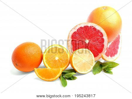 Colourful fresh slices of ripe orange and tasty, appetising round grapefruit and sour, juicy lemon with green citrus leaves, isolated on a white background. Tropical, organic, fresh citrus fruit.