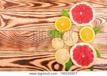 Two juicy, fresh and bright red grapefruit slices and two slices of ripe, sweet and delicious oranges and three small, round, appetite and sour lobes of lemon with green leaves on a light wooden table