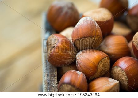 Pile of whole hazelnuts in wood box on garden table close up vibrant color top view view cozy autumn atmosphere inspirational