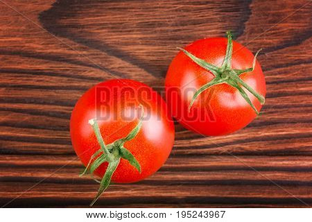 Two perfect ripe, juicy, fresh and bright red tomatoes with green leaves on a dark wooden table background. Fresh cherry tomatoes. Organic, ripe and juicy tomatoes. Delicious and useful vegetables.