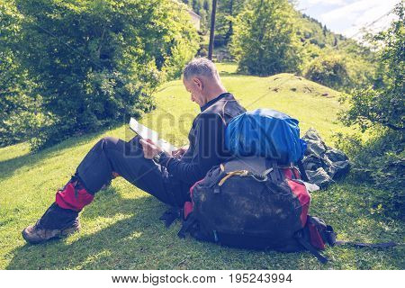 Man Traveler Sits On An Alpine Meadow With Map