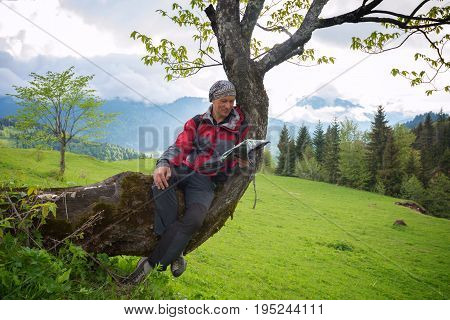 Happy Man Traveler Is Resting, Sitting On A Tree