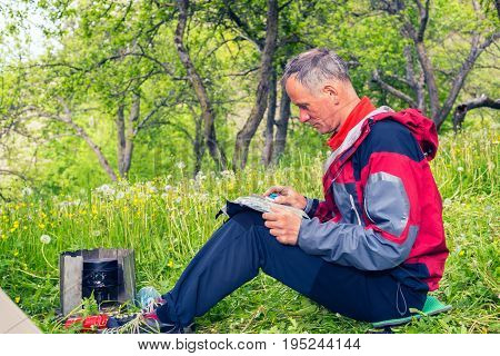 Puzzled Traveler Sits On A Green Meadow