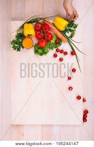 Tasteful vegetables on a spacious light brown wooden table. A hand holding a fresh yellow salad pepper. A glass full of organic orange juice. Healthy and delicious eating. Food for vegetarians.