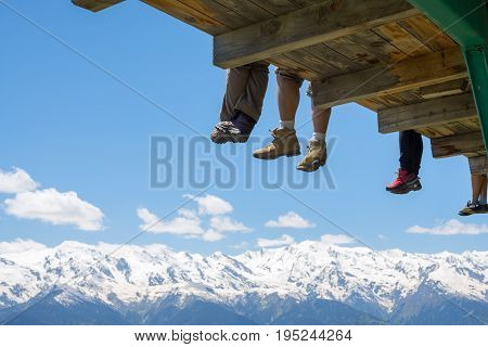 Legs of joyful travelers over the mountain gorge against the backdrop of snow-capped mountain ranges and deep blue sky. Happy friends relax after climb in the mountains.