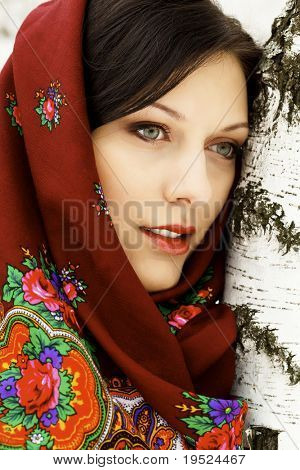 Gorgeous russian woman in shawl standing by the birch