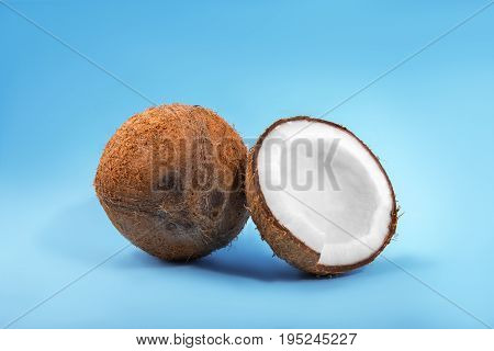 Close-up healthful coconuts on a light blue background. Hawaiian coconut cut in pieces. Organic ingredients for cooking vegan meals. Nutritious exotic nuts.