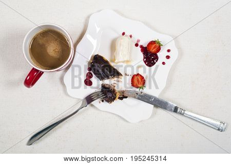 Breakfast with coffe and leftover of eclair cake.Top view