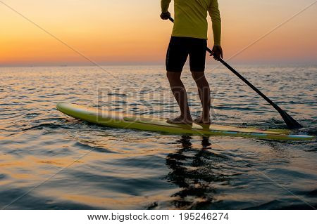 SUP silhouette of athletic man standing with a paddle on the surfboard at sunset stand up paddle boarding legs