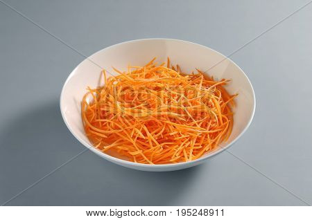 Bowl with grated carrot portion isolated on grey background