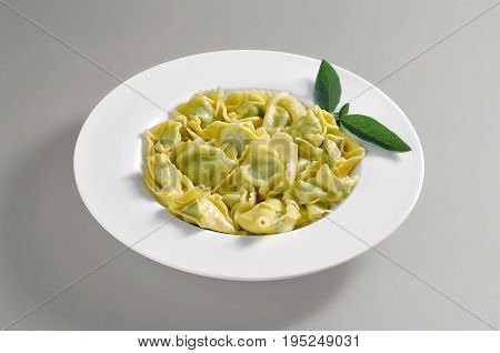 Dish with portion of ravioli with butter and sage isolated on grey background
