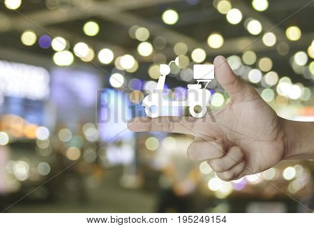 Motor bike icon on finger over blur light and shadow of shopping mall Business delivery service concept