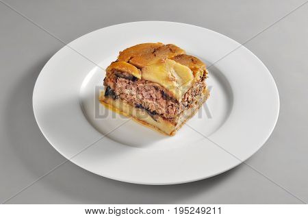 Round dish with a portion of Greek moussaka isolated on grey background