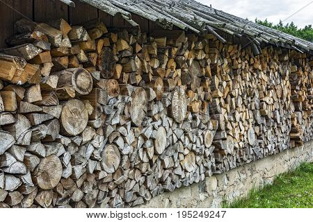 Under a canopy stacked firewood in a woodpile for the winter season