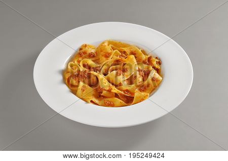 Round dish with a serving of pappardelle pasta with meat souce on grey background