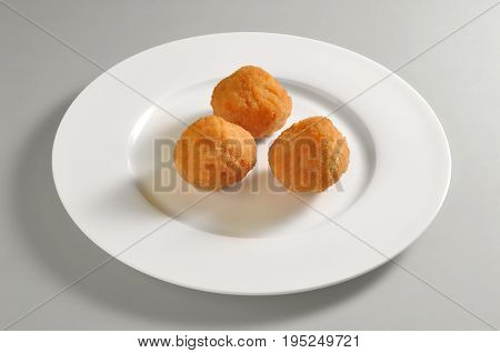 Round dish with fried breaded rice balls isolated on grey background